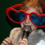 Small girl singin karaoke with funny glasses and big smile
